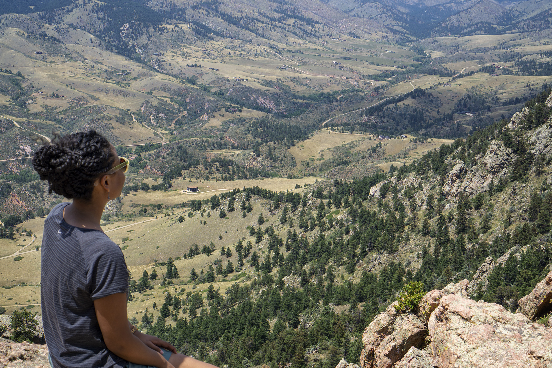 Black woman looking out onto valley from top of Horsetooth Rock, Colorado / Darker than Green
